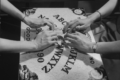 People playing with a Ouija Board.  (Pho